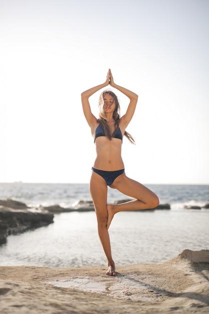 Haciendo yoga en la playa Foto Premium