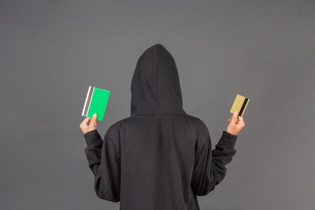 Hacker lleva una tarjeta de crédito dorada y un libro bancario Foto gratis