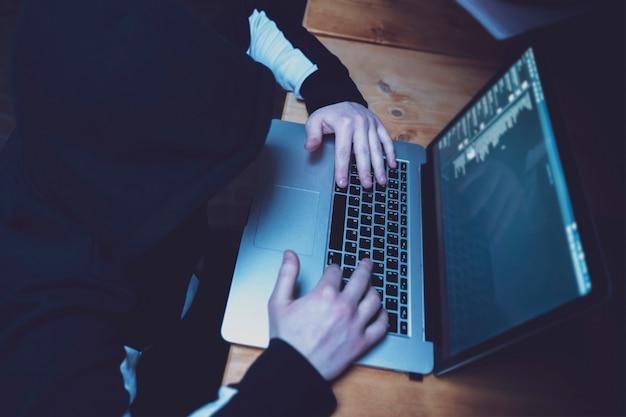 Hacker masculino que usa una computadora portátil, rompiendo los servidores del gobierno con datos personales. Foto Premium