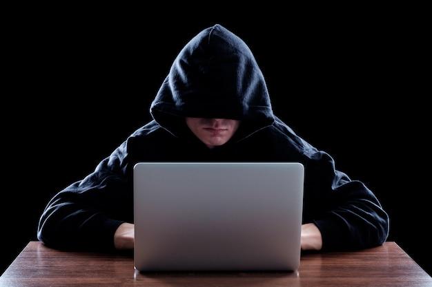 Hacker en una oscura sudadera con capucha sentado frente a un cuaderno Foto Premium