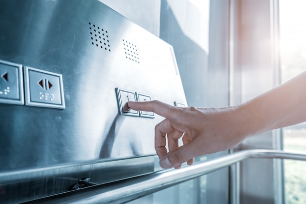 Haga clic en el botón del elevador con el dedo. Foto Premium