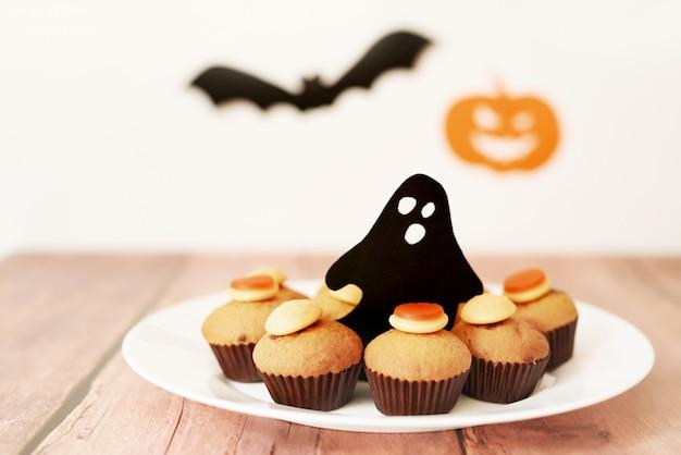 Halloween trata cupcakes en la mesa contra el fondo de calabazas y murciélagos Foto Premium