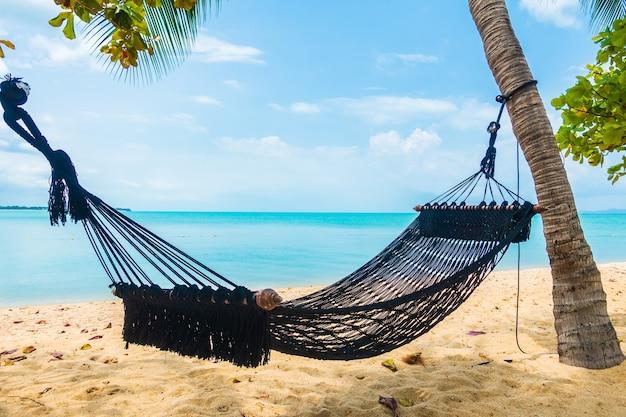Hamaca vacía columpio alrededor de la playa, mar, océano, con nubes blancas, cielo azul para viajes de vacaciones Foto gratis