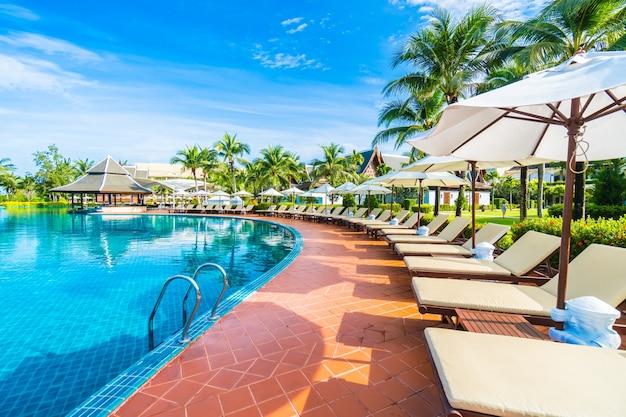 Hamacas y sombrillas puestas cercas de una piscina grande for Sombrillas para piscinas
