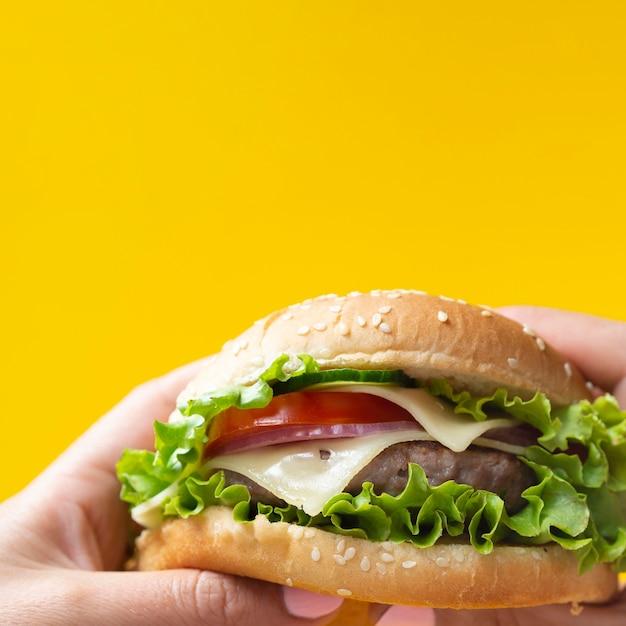 Hamburguesa apetitosa sobre fondo amarillo Foto gratis