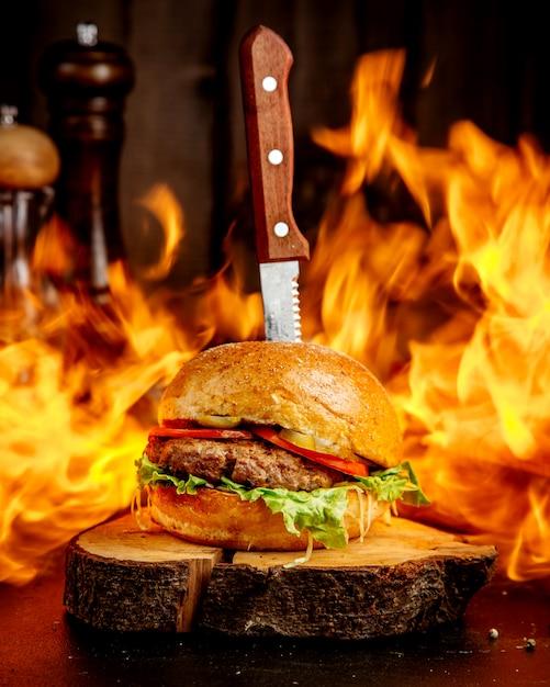Hamburguesa de carne de fuego en un cáñamo de madera Foto gratis