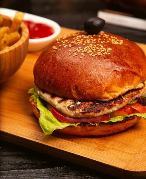 Hamburguesa de carne de pollo con rodajas de tomate y lechuga servida con papas fritas, salsa de tomate y mayonesa en una tabla de madera Foto gratis
