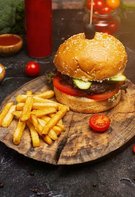 Hamburguesa de carne sabrosa fresca y papas fritas en mesa de madera, ketchuo, tomates, vegetales Foto gratis