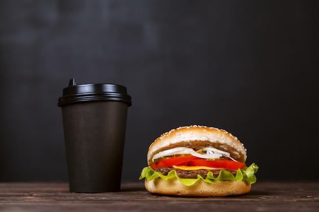 Hamburguesa de la carne de vaca con tocino y café en una taza de papel negra en una tabla de madera. concepto de diseño de menú de cafetería Foto Premium