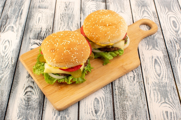 Una hamburguesa de carne de vista frontal con queso y ensalada verde en la mesa de madera y mesa gris Foto gratis