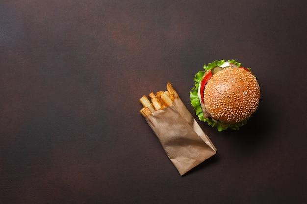 Hamburguesa casera con ingredientes de carne de res, tomates, lechuga, queso, cebolla, pepinos y papas fritas sobre fondo oxidado Foto Premium