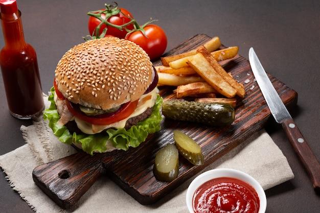 Hamburguesa casera con ingredientes de ternera, tomate, lechuga, queso, cebolla, pepino y papas fritas Foto Premium