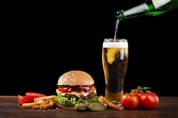 Hamburguesa casera con papas fritas y una botella de cerveza vertiendo en un vaso. Foto Premium