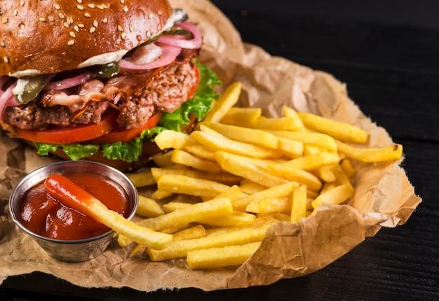 Hamburguesa clásica para llevar con papas fritas y salsa de tomate Foto gratis