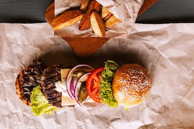 Hamburguesa descompuesta en sus componentes en papel kraft sobre una mesa de madera. paquete de chips. Foto Premium