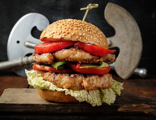 Hamburguesa doble casera con filete de cerdo frito, tomates rojos, pan redondo fresco Foto Premium