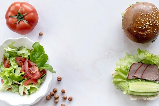 Hamburguesa; ensalada de vegetales; tomate entero avellana sobre superficie blanca Foto gratis