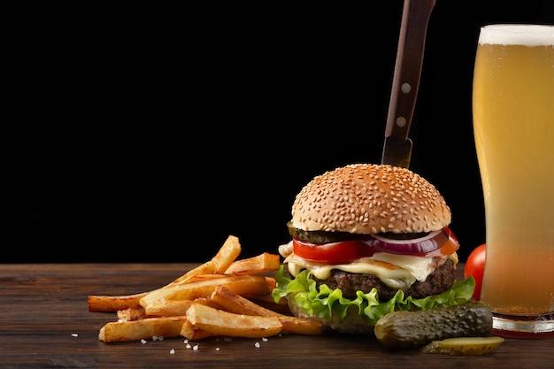 Hamburguesa hecha en casa con las patatas fritas y el vidrio de cerveza en la tabla de madera. en la hamburguesa se clavó un cuchillo. Foto Premium