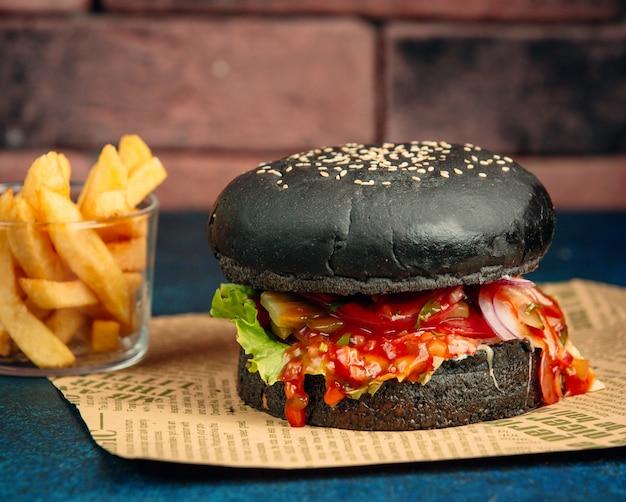 Hamburguesa negra con salsa de tomate, lechuga, cebolla, tomate y papas fritas. Foto gratis