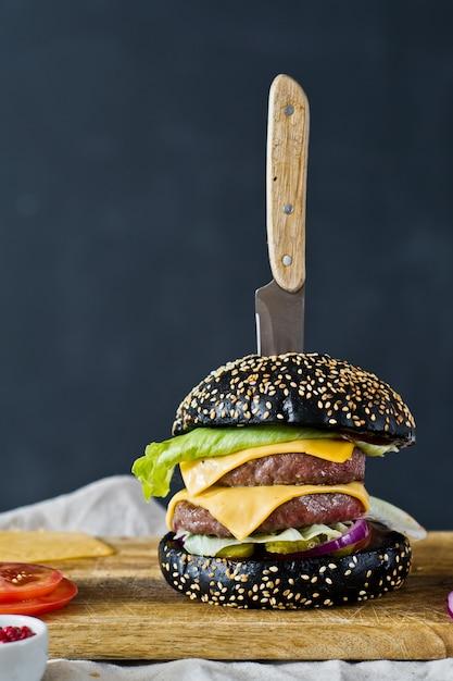 Hamburguesa negra en una tabla de cortar de madera. Foto Premium