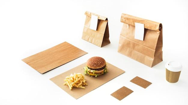 Hamburguesa y papas fritas sobre papel con bebida desechable y paquete de papel sobre fondo blanco Foto gratis