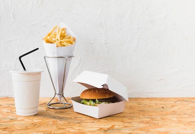 Hamburguesa; papas fritas y vaso desechable en mesa de madera Foto gratis