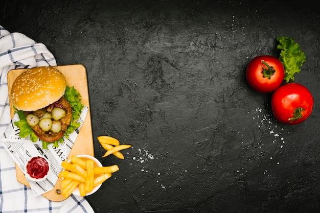 Hamburguesa plana y papas fritas sobre tabla de madera con copyspace Foto gratis