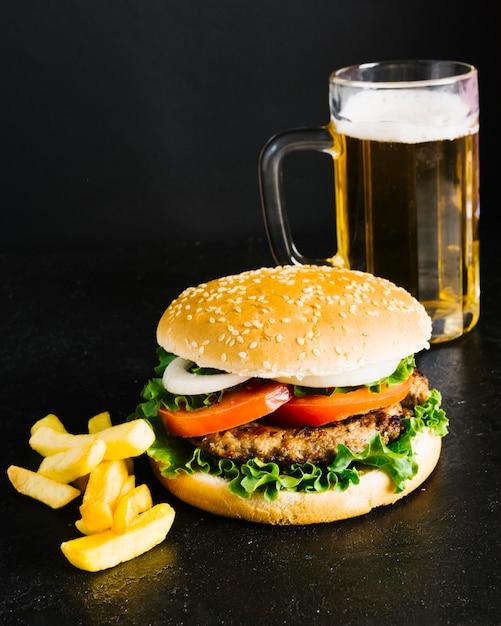 Hamburguesa de primer plano de alto ángulo con papas fritas y cerveza Foto gratis