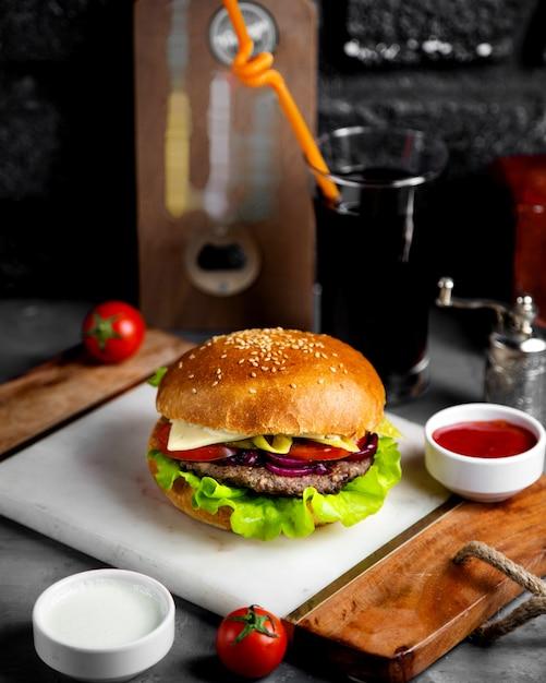 Hamburguesa con queso y carne con cebolla y pepinillos Foto gratis
