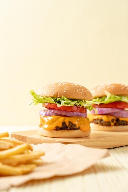 Hamburguesa de ternera fresca y sabrosa con queso y papas fritas Foto Premium
