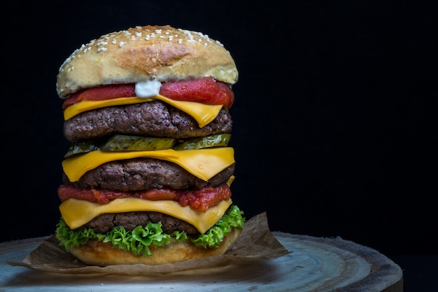 Hamburguesa triple con tomate, lechuga, pepinillos y mayonesa Foto Premium