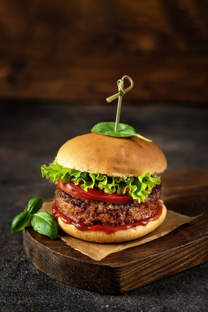 Hamburguesa vegana en superficie marrón rústica oscura Foto Premium