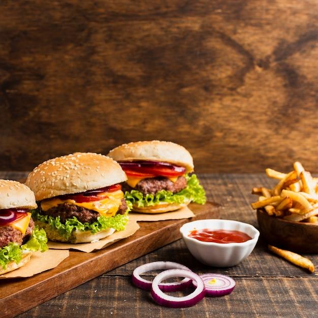 Hamburguesas en bandeja de madera con papas fritas Foto gratis