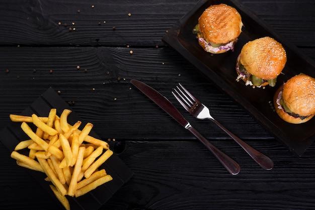 Hamburguesas de comida rápida con papas fritas y cubiertos Foto gratis