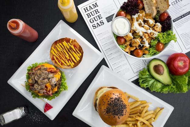 Hamburguesas, papas fritas, ensaladas y menú de restaurante. Foto Premium
