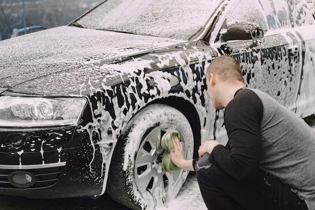 Handsomen hombre en un suéter negro lavando su auto Foto gratis