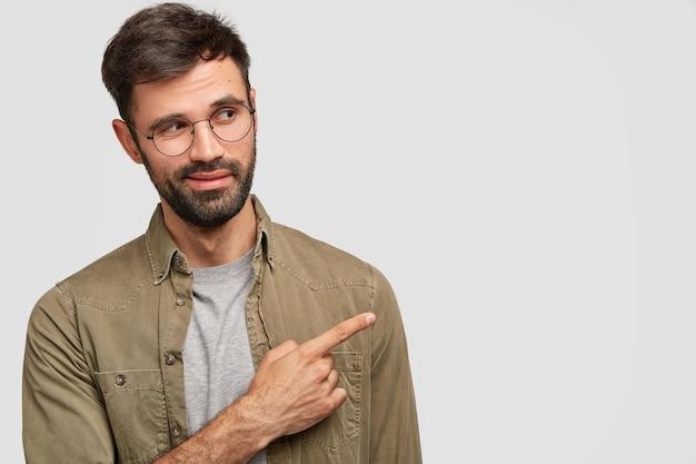 Hansome un varón caucásico sin afeitar mira con curiosidad a un lado, indica con el dedo índice en la esquina superior derecha Foto gratis