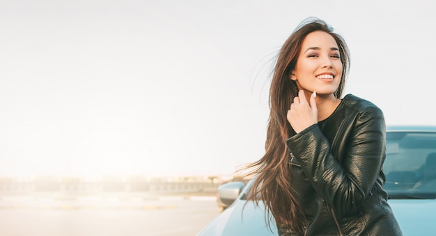 Happpy hermosa encantadora morena de pelo largo joven asiática en chaqueta de cuero negro Foto Premium