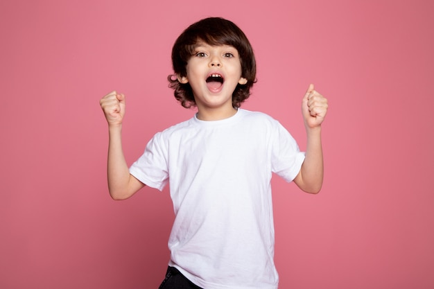 Happy boy little cute adorable en camiseta blanca y jeans azul sobre rosa Foto gratis