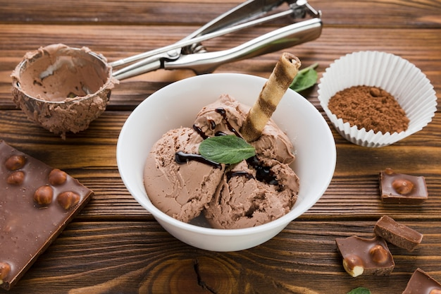 Helado de chocolate en un tazón en la mesa de madera Foto gratis