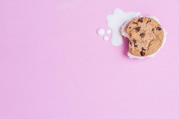 Helado derretido y galleta sobre fondo rosa espacio de copia Foto gratis