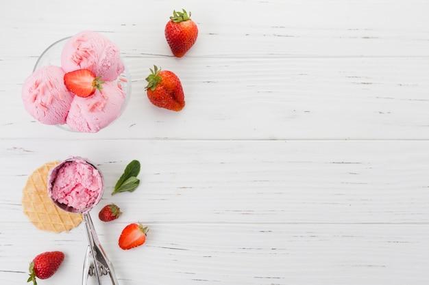Helado de fresa en un tazón en superficie de madera Foto gratis