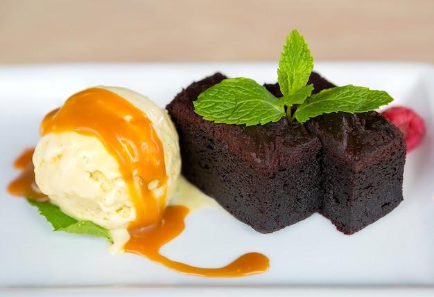Helado de vainilla con brownies hojas de menta postre de salsa de frambuesa y caramelo Foto Premium