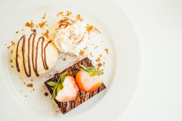 Helado de vainilla con pastel de brownie de chocolate con fresa en la parte superior Foto gratis