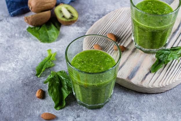 Helathy green smoothie con nueces de manzana verde, espinaca, kiwi y almendra sobre fondo de hormigón gris. Foto Premium