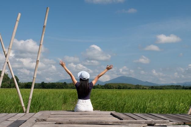 Hembra adolescente sentado en el puente de madera en el campo de arroz concepto diversión solo relajación viaje estilo de vida Foto Premium