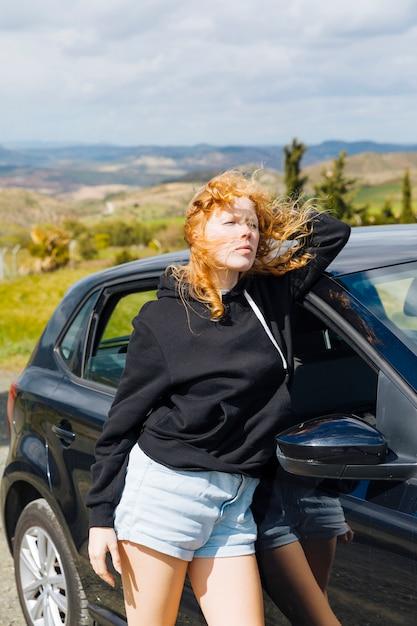 Hembra joven que se coloca cerca del coche negro Foto gratis