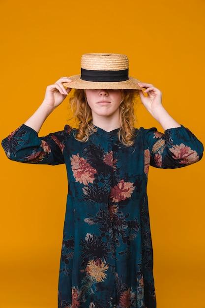 Hembra joven en vestido con sombrero beige Foto gratis