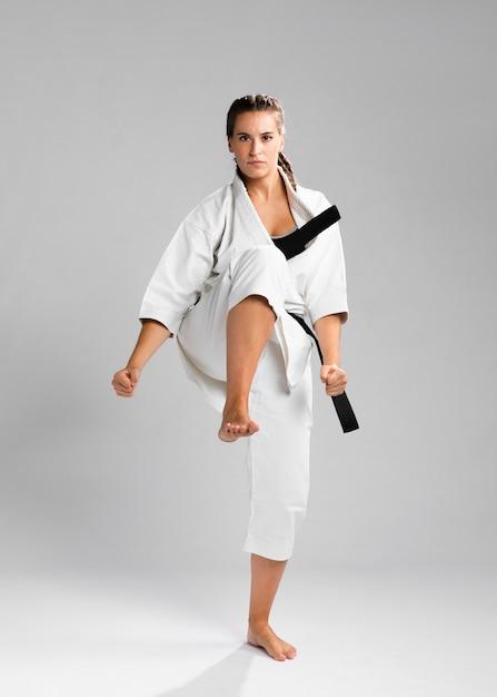Hembra en posición de combate vistiendo el uniforme blanco sobre fondo gris Foto gratis