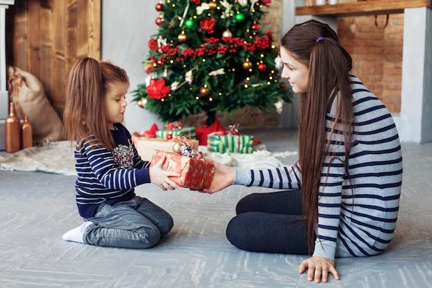 Hermana feliz desempacar regalos para navidad. Foto Premium